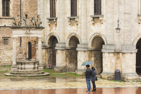 montepulciano: Montepulciano,Italy-April 23,2016:a couple under the umbrella admire and take photograph under the rain in the town square of Montepulciano during a cloudy day.
