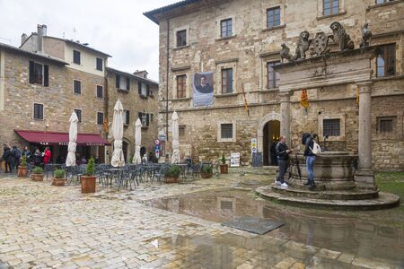 montepulciano: Montepulciano,Italy-April 23,2016:people stroll under the rain in the town square of Montepulciano during a cloudy day. Editorial