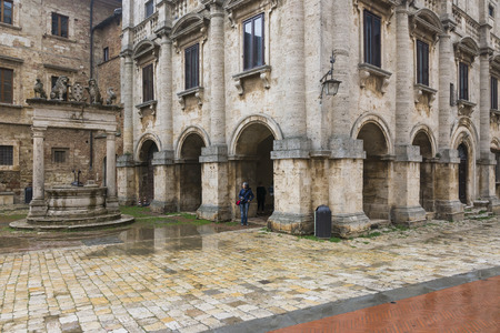 cloudy day: Montepulciano,Italy-April 23,2016:people stroll under the rain in the town square of Montepulciano during a cloudy day. Editorial