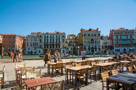 gondoliers: Venice,Italy-August 17,2014:people stroll or take a rest near the bar and restaurant on Grand canal near the Rialto bridge  during a sunny day. Editorial