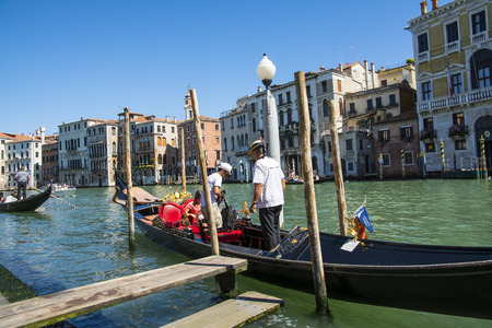 gondoliers: Venice,Italy-August 17,2014:Venetian gondoliers carry around some tourists  on a gondola in Venice During a sunny day inside her famous canals.