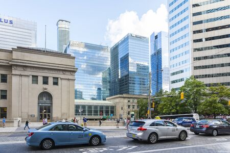 urban sprawl: Toronto,Canada-august 1,2015:view of traffic and skyscrapers in Toronto during a sunny day from une of the central street of the city.