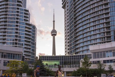 urban sprawl: Toronto,Canada-august 2,2015:Urban life  near the CN tower in Toronto during a sunset from one of the central street of the city Editorial