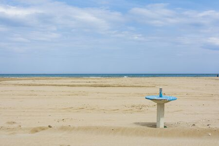 Rimini,Italy-April 17,2015:a solitary table submerged by sand on the beach in Rimini in Italy during a cloudy day