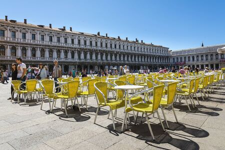 Venice,Italy -August 17,2014:people stroll in the famous saint Mark square in Venice near the bar with the yellow chairs during a sunny day.