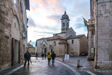 San Quirico dOrcia,Italy-april 24,2016:people stroll near the church in the  San Quirico town square during a cloudy day.