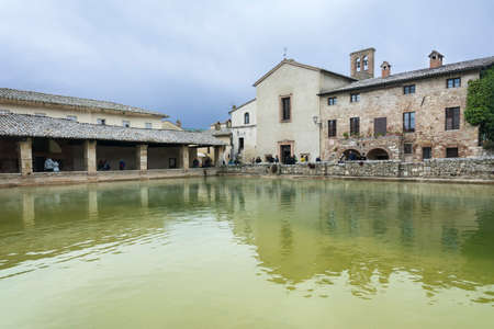 Bagni Vignone,Italy-April 25,2016:People visit the little town in tuscany,Italy famous for the sulphurous hot springs during a cloudy day. Editorial