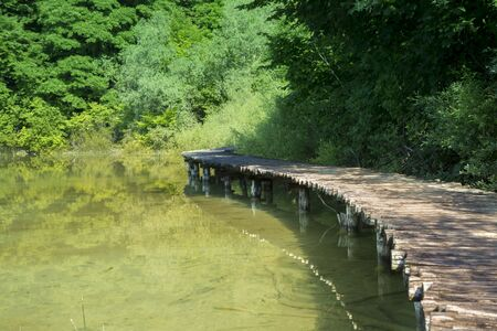 Pedestrian walkway on water in the national park of plitvice lakes in croatia on a sunny day Stock Photo
