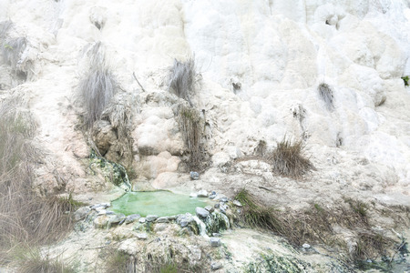 Limestone formations at the hot springs of the Bagni di San Filippo in Tuscany, Italy, during a sunny day.