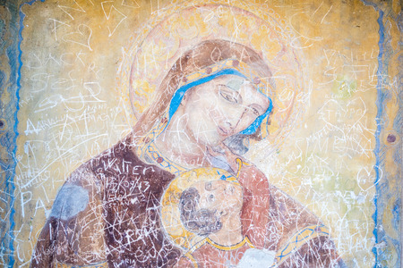 Painting of the Madonna ruined by writings of tourists Editorial