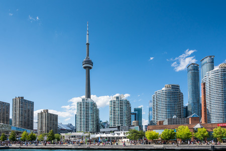 Toronto,Canada-august 3,2015:people stroll along the lakefront with the Toronto skyline behind them during a sunny day.