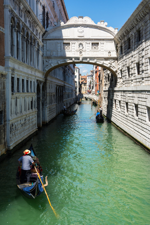 Venice,Italy -August 17,2014:A gondola passes under the bridge of sighs in Venice during a sunny day Editorial