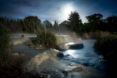 Night view of the famous free spa of the mill in Saturnia in Tuscany, Italy. A series of natural pools of hot water where people relax Banco de Imagens