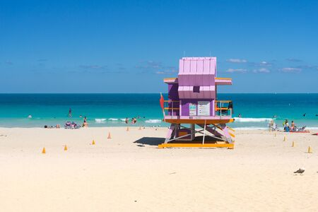 Miami,USA-march 15,2018:people near of one of the famous and colorful beach guard cabins on Miami beach during a sunny day