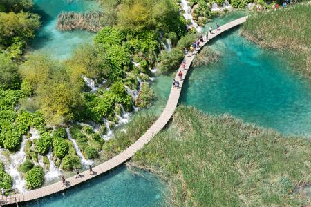 top view of people on classic wooden walkways crossing lakes in Plitvice natural park during a sunny day