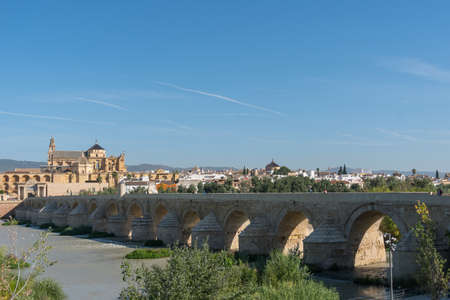 Cordoba, Spain-august 11, 2017: view of the old roman bridge that crosses the Guadalquivir River and the cathedral during a sunny day.