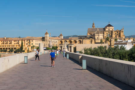 Cordoba, Spain-august 11, 2017: people on the old roman bridge that crosses the Guadalquivir River and the cathedral during a sunny day.