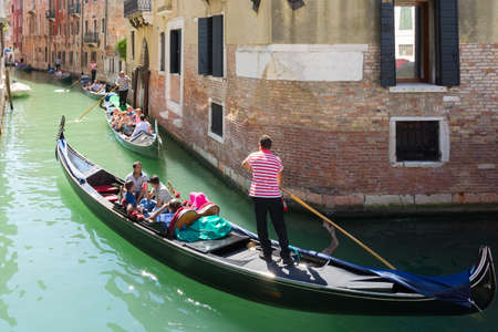 Venice, Italy-August 17,2014: This is a typical view of Venice with its canals and narrow streets full of tourists during a sunny day.