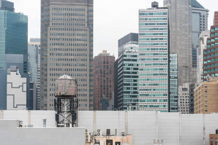 New York City, USA - August 6, 2019: Daily life in New York city during a cloudy day.Here a view of skyscrapers and old water tank