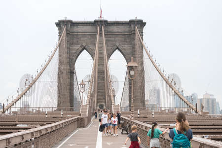 New York City, USA - August 6, 2019: People walk across the famous Brooklyn Bridge during a cloudy day.
