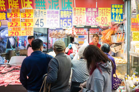Hong Kong, March 24,2019: People among the classic markets in the narrow and crowded streets of Hong Kong during a cloudy day