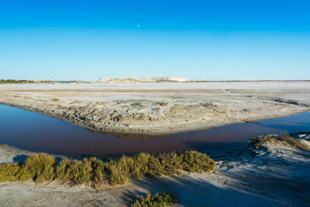 View of a canal that crosses a salt pan in the Camargue during a sunny day