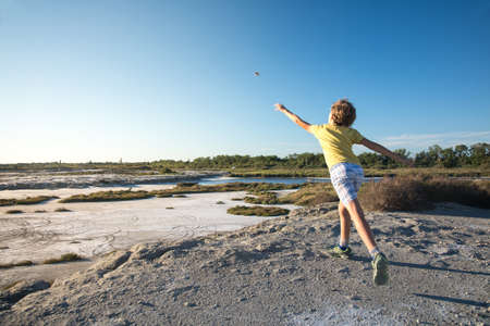 Child throws a stone in the Camargue landscape during a sunny day Redactioneel