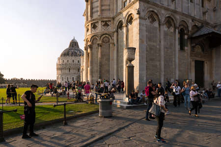 Pisa, Italy-October 21, 2018: tourists stroll and admire Piazza dei miracoli in Pisa at sunset