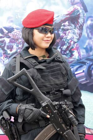 kevlar: Jakarta, Indonesia - December 13, 2014: Elite force girl in uniform with small machine gun Editorial
