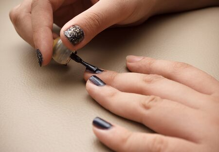 gently: Someone gently applying black color nail polish using a brush to make a beautiful nail art. This image was shot with single flash light bouncing technique