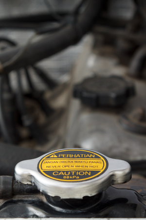 bilingual: Radiator cap with bilingual warning messages on its label. It says to never open the cap when in hot condition. Printed in Bahasa Indonesia and English. Stock Photo