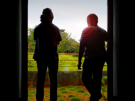 conversing: Silhouette of two men who standing at the front door while conversing each other. Stock Photo