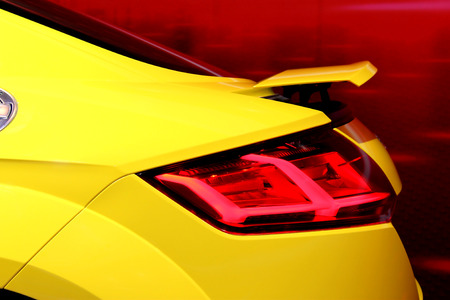 aerodynamic: Rounded curves and a duck-tail on a yellow sports car makes it more aerodynamic (less drag) and stable on the road.