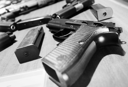 handguns: Semi-automatic handguns or pistols and its magazines. The gun at the near side is a P2 pistol which made in Indonesia. Black and white photography.