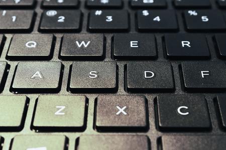 side lighting: Left side of island styled laptops keyboard. Shot in closed distance with single lighting technique.