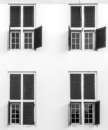 open windows: Open windows on a building viewed from outside. Black and white photography.