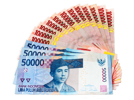 Piles of Indonesian Rupiah (IDR) banknotes on the white background.