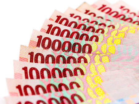 necessity: Piles of Indonesian Rupiah (IDR) banknotes on the white background.
