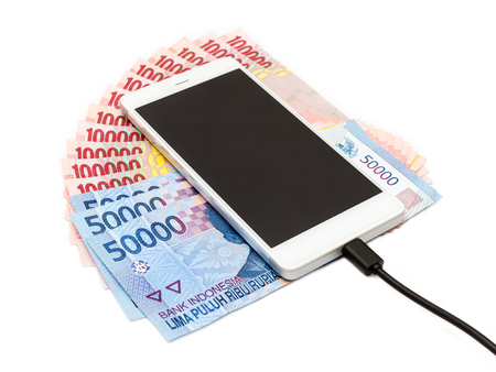 transmitting device: Smartphone above the piles of Indonesian Rupiah (IDR) banknotes on the white background.