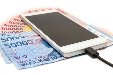 Smartphone above the piles of Indonesian Rupiah (IDR) banknotes on the white background.