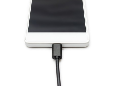 transmitting device: Micro USB data cable connected to the smartphone. White background isolated. Stock Photo
