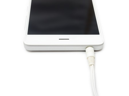Mini audio cable connected to the smartphone. White background isolated.