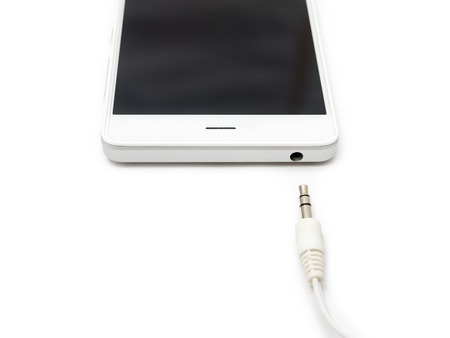 Mini audio cable disconnected from the smartphone. White background isolated.