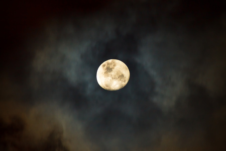 The moon covered by the clouds at cloudy night in the monsoon season. Long exposure photography. Stock Photo