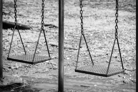 Empty swing sets facility on the park that puddled with water on its below after raining. Black and white photography.