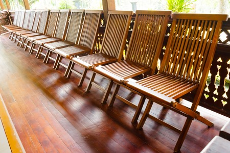 Empty wooden folding chairs are arranged sideways on the wooden floor. The chairs are brown colored. Stock Photo