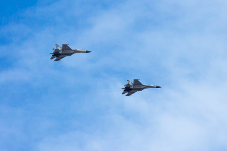 A couple of combat aircrafts flyby in an airshow with blue sky on the background. They are consist of single seat and double seats Sukhoi Su30 fighter jets.