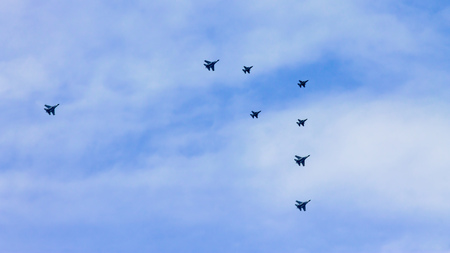 Formation of an aerobatic team aircrafts flyby in an airshow. They are eight planes which consist of four Sukhoi Su30 and four Lockheed Martin F-16 fighter jets.