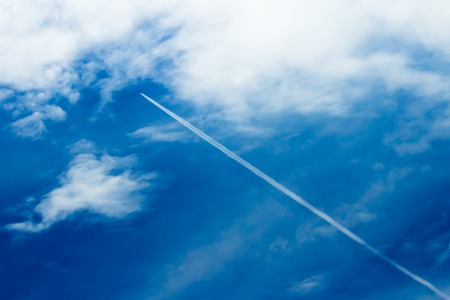 Long contrail from aviation engine in the blue sky. Contrail is a nature phenomena which made from condensationed hot gas that produced from the aviation engine which fly high at the thin cool air layer in atmosphere. Stock Photo