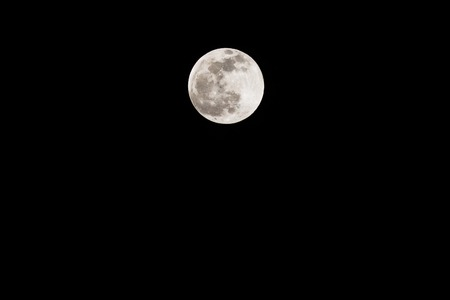 Full moon isolated in the dark sky. The bright and the dark colors shows the moon surface. Stock Photo